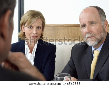 Middle aged business people in serious discussion at restaurant - stock photo