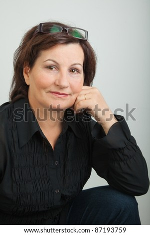 Middle aged business woman dressed in black on grey background. - stock photo