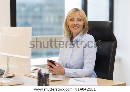 Middle aged business woman working at office. Using smartphone - stock photo