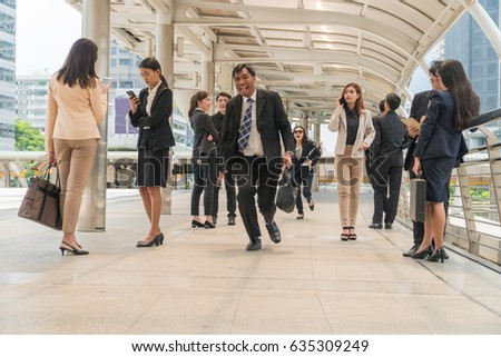 Middle-aged businessman carrying a briefcase, running in a hurry to go to work among the people walking in city.