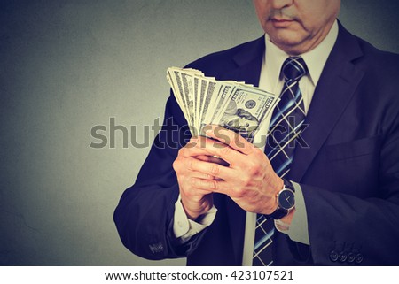 Middle aged businessman counting money - stock photo