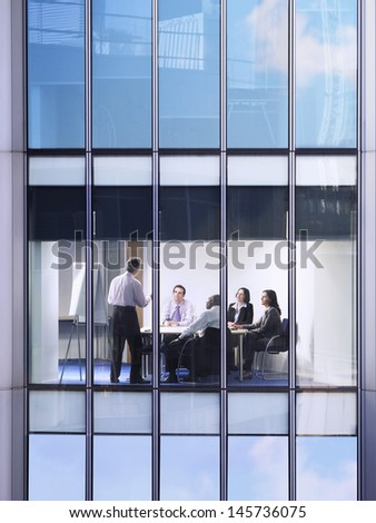 Middle aged businessman giving presentation to colleagues in conference room - stock photo