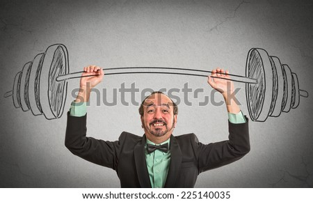 middle aged businessman holding hand sketched barbell. Achievements in business, aim high, crazy assignment, difficult impossible task made possible concept. Grey wall background. face expression - stock photo