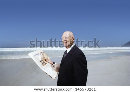 Middle aged businessman holding newspaper on beach - stock photo