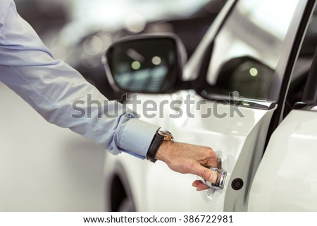Middle aged businessman in classic shirt is opening a car in a motor show, close-up - stock photo