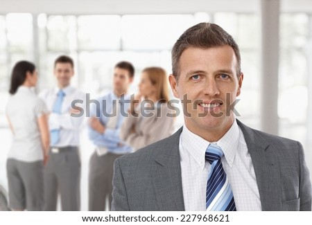 Middle-aged businessman in front, business team talking in background. - stock photo