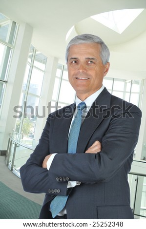 Middle Aged Businessman in Lobby of Building with His Arms Folded - stock photo