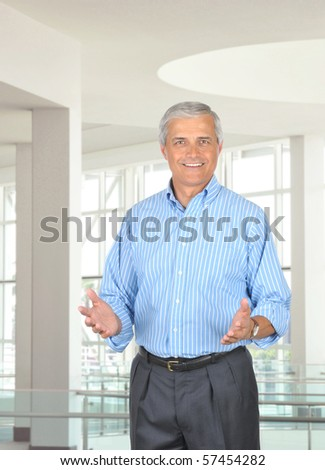 Middle aged businessman in modern office setting gesturing with both hands. Vertical format with 3/4 view of man who is smiling. - stock photo