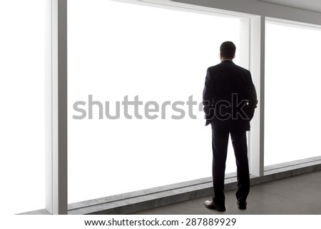 Middle aged businessman looking out a bright office window and thinking - stock photo