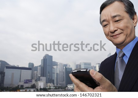 Middle aged businessman reading text message on cell phone with cityscape in background - stock photo