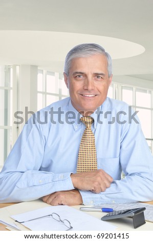 Middle aged Businessman Seated at His Desk in Modern Office Setting. Man is wearing a blue dress shirt and yellow tie with no jacket. Vertical format - stock photo