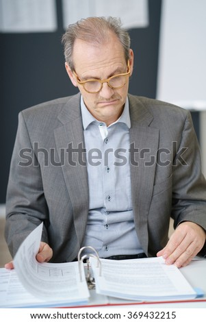 Middle-aged businessman sitting at a desk reading his notes in an office binder with a serious expression - stock photo