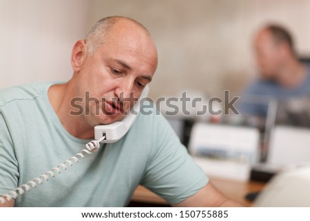 Middle-aged businessman  speaking on the phone and working in the office - stock photo