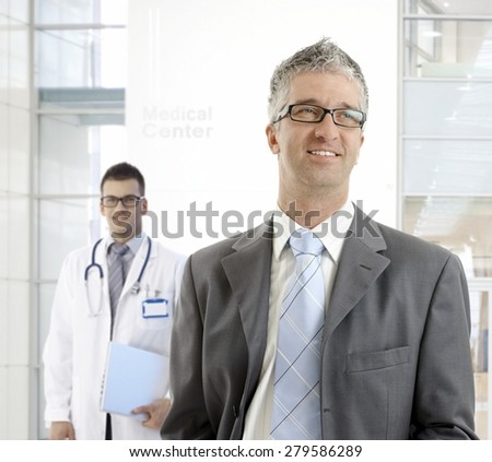 MIddle-aged businessman standing at medical center, smiling, looking away.