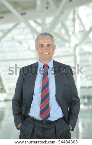 Middle aged businessman standing in modern office lobby with his hands in pockets. Vertical format with man smiling at the camera. - stock photo