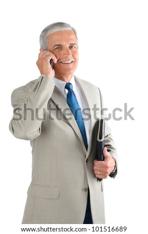 Middle aged businessman talking on his cell phone and carrying a binder. Man is smiling and looking at camera over a white background. - stock photo