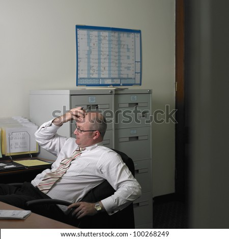 Middle-aged businessman thinking at his desk