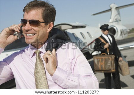 Middle aged businessman using cell phone with driver holding luggage in the background at airfield - stock photo