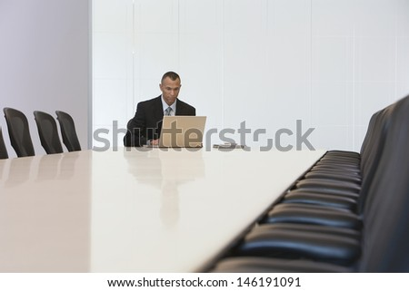 Middle aged businessman using laptop in board room