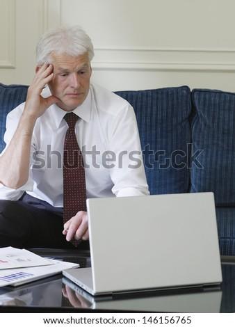 Middle aged businessman using laptop while sitting on sofa - stock photo