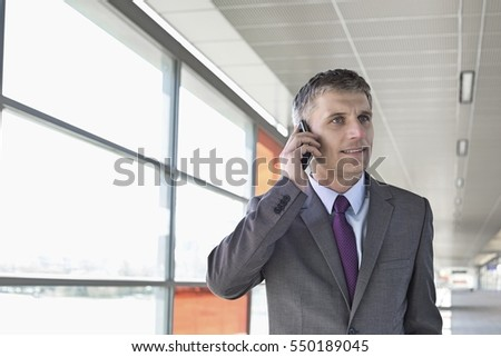 Middle aged businessman using mobile phone at train station