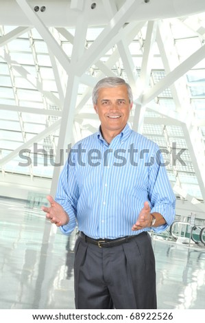 Middle aged businessman wearing Striped Blue Shirt Gesturing with Both Hands in modern office setting. Vertical Format. - stock photo