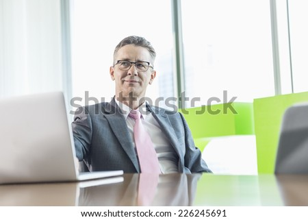 Middle-aged businessman with laptop sitting at conference table - stock photo