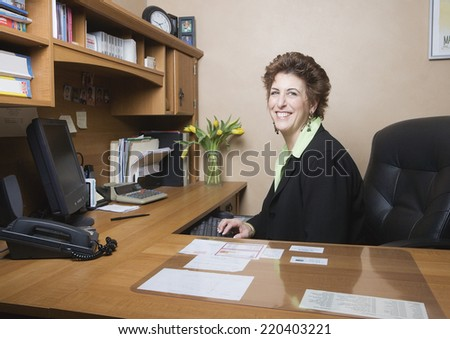 Middle-aged businesswoman at desk - stock photo