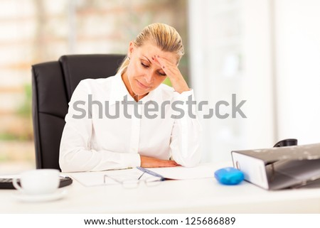 middle aged businesswoman looking worried when reading sales report - stock photo