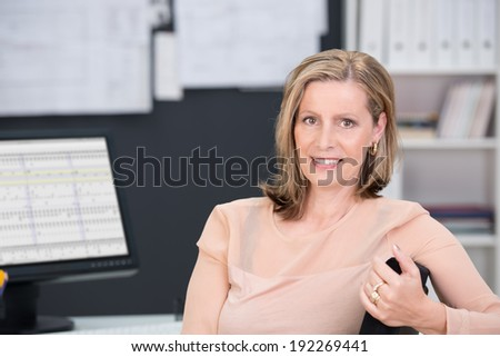 Middle-aged businesswoman sitting at her desk turning with her arm over the back of her office chair to smile at the camera - stock photo