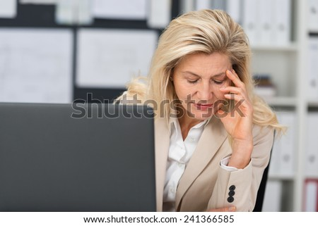 Middle-aged businesswoman suffering a stress headache sitting at her desk leaning her head on her hand with her eyes closed in pain