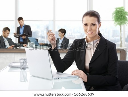 Middle-aged businesswoman with laptop at office desk, smiling. - stock photo