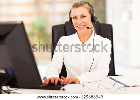 middle aged businesswoman working in office with headphones on - stock photo