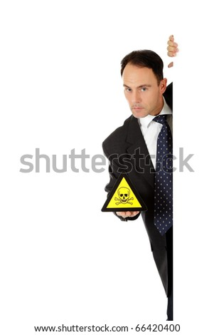 "Middle aged caucasian businessman behind wall showing warning sign ""hazardous/toxic material"". Copy space. Studio shot. White background."
