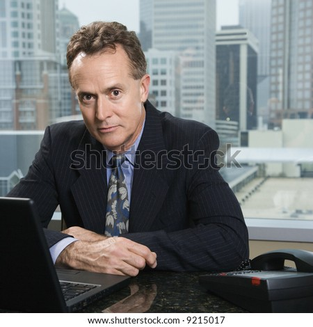 Middle-aged Caucasian male in office with skyline in background. - stock photo