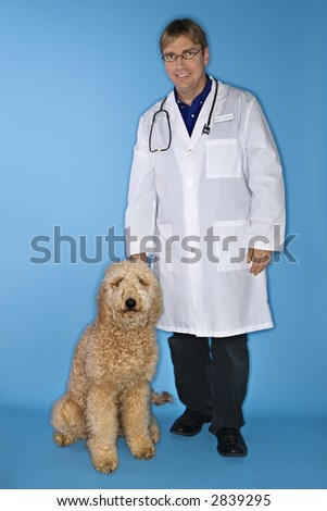 Middle-aged Caucasian male veterinarian with Goldendoodle dog. - stock photo