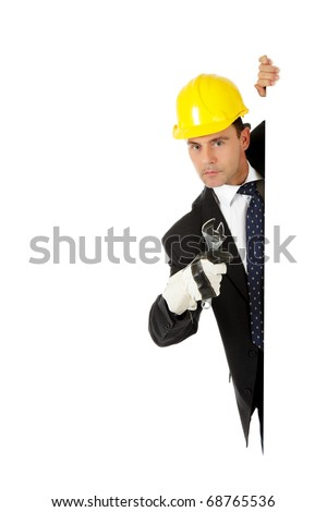 Middle aged caucasian man behind wall equipped with protective glove and helmet  holding a plumber spanner. Copy space. Studio shot. White background. - stock photo
