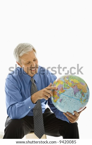 Middle aged Caucasian man holding globe and pointing. - stock photo