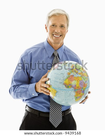 Middle aged Caucasian man holding globe and smiling at viewer. - stock photo