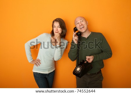 Middle aged Caucasian man on telephone while woman listens to the conversation