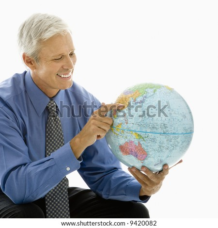 Middle aged Caucasian man pointing on globe. - stock photo