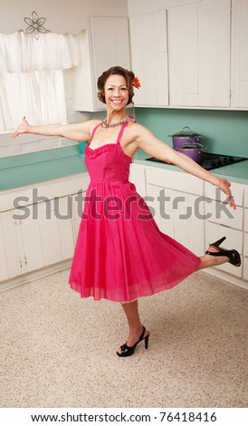 Middle aged Caucasian woman dances in a kitchen - stock photo