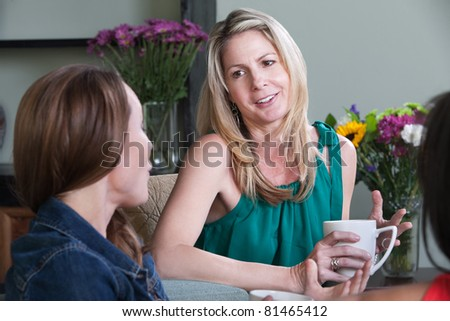 Middle-aged Caucasian woman enjoys cup of coffee with friends