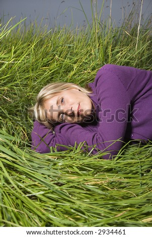 Middle-aged Caucasian woman lying on side in grass.