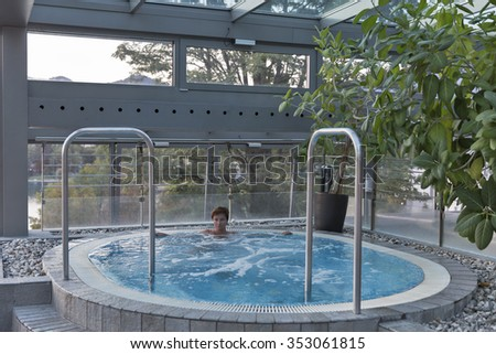 Middle aged Caucasian woman relaxing in jacuzzi with big window