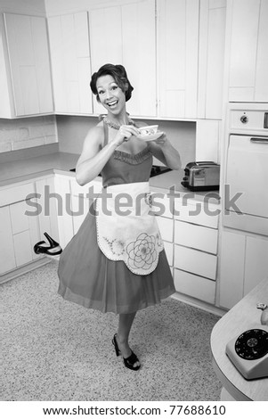 Middle-aged Caucasian woman standing on one foot in kitchen - stock photo