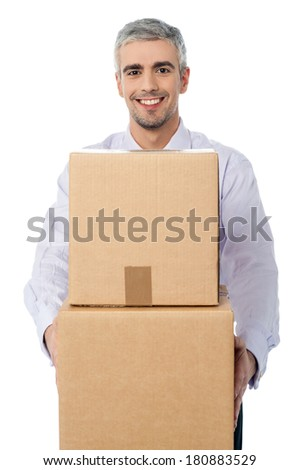 Middle aged corporate man holding stack of boxes