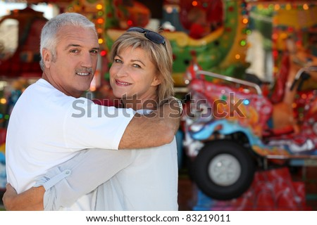 Middle-aged couple at funfair - stock photo