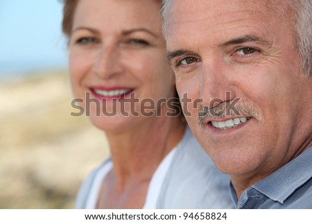 Middle-aged couple at the beach - stock photo
