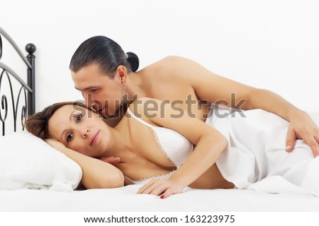Middle-aged couple awaking in bed at bedroom - stock photo